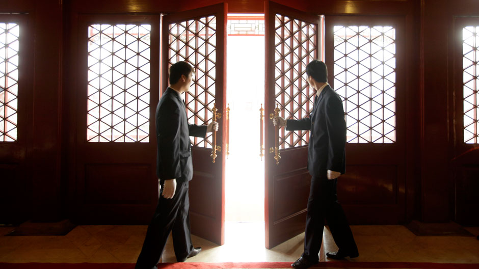 Waiters open a Chinese traditional red door inside a luxurious furniture museum in Beijing February 5, 2010