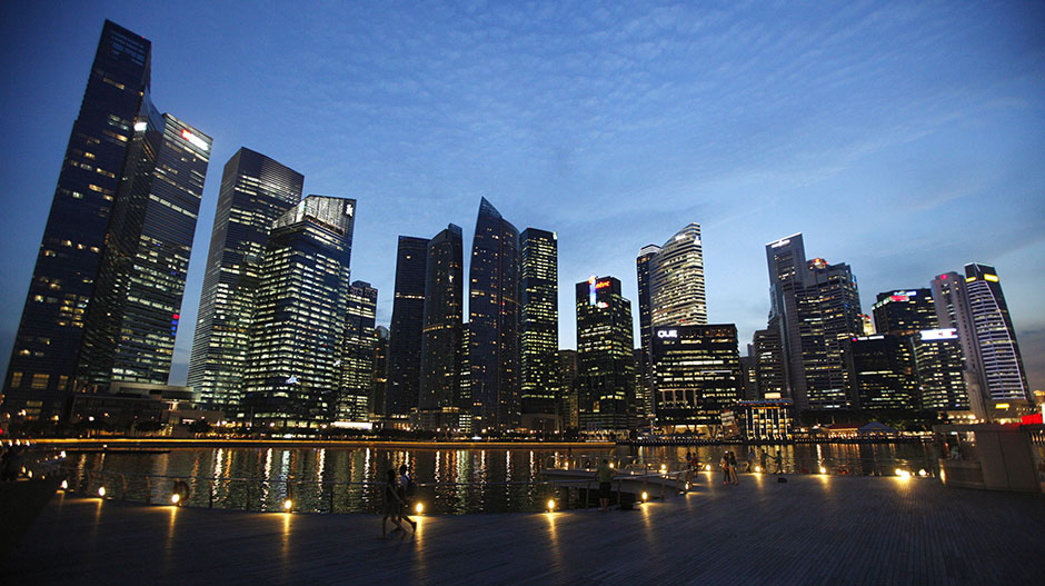 People walk past the skyline of Marina Bay central business district in Singapore April 26, 2013.